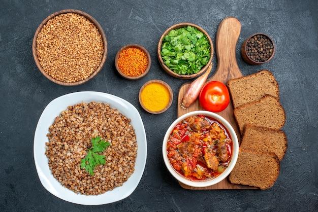 Вид сверху вкусной приготовленной гречки с приправами и буханками хлеба на сером