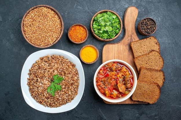 Vista dall'alto gustoso grano saraceno cotto con condimenti e pane su grigio