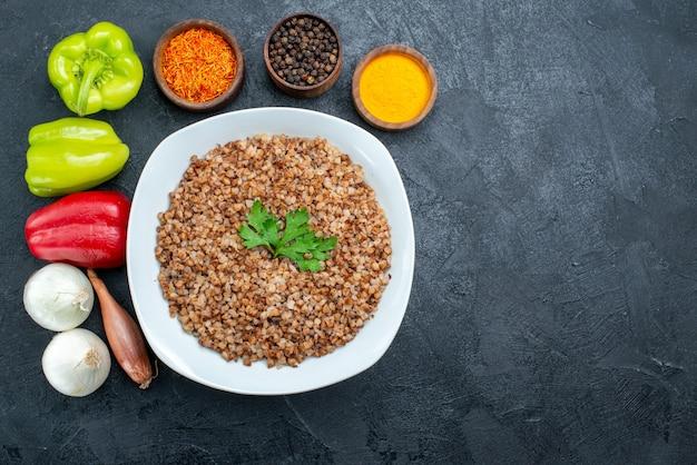 Top view tasty cooked buckwheat with seasonings on grey