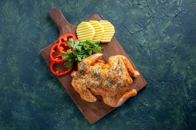 トップビューダークバックグラウンドカラーの料理ディナーミールフードバーベキューにジャガイモとスライスしたコショウでスパイスを効かせたおいしい調理済みチキン
