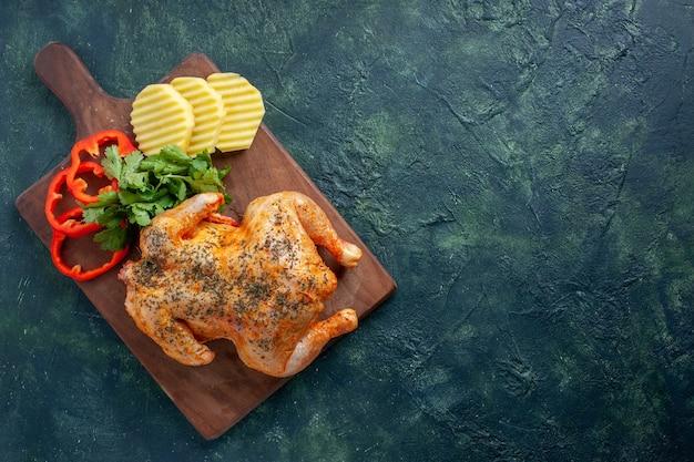 暗い背景にジャガイモとスライスしたコショウでスパイスを効かせたおいしい調理済みチキンの上面図肉色料理ディナー食事食品バーベキュー無料の場所