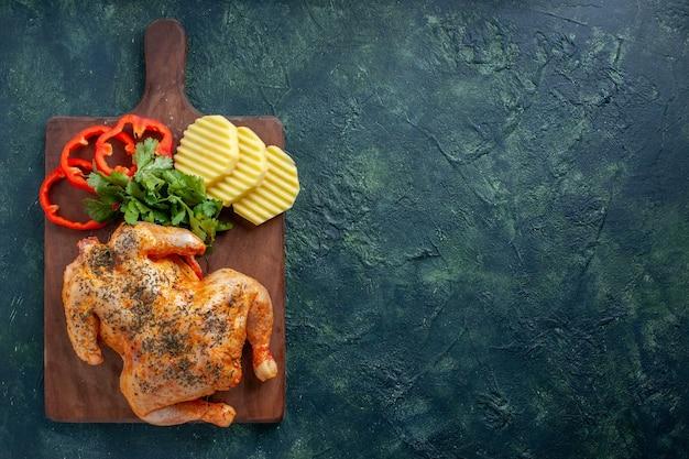 暗い背景にジャガイモとスライスしたコショウでスパイスを効かせたおいしい調理済みチキンの上面図肉色料理ディナー食事食品バーベキューの空きスペース