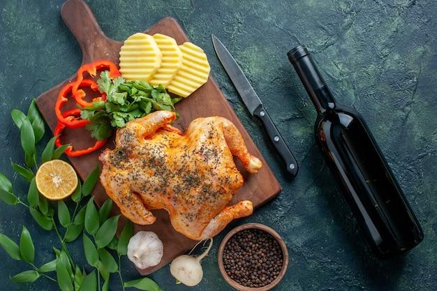 Vista dall'alto gustoso pollo cotto condito con patate su sfondo scuro colore carne piatto cena ristorante barbecue cibo vino