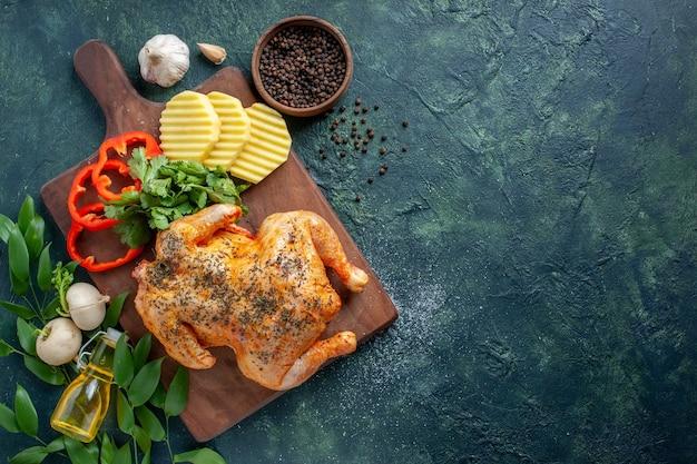 暗い背景にジャガイモでスパイスを効かせたおいしい調理済みチキンの上面図肉色料理レストランバーベキュー料理夕食の食事