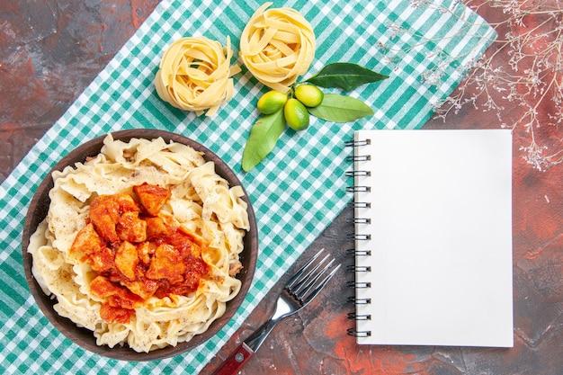 Вид сверху на вкусное приготовленное тесто с курицей и соусом на темной поверхности блюда для макаронных изделий