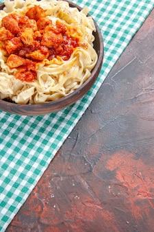 Vista dall'alto gustoso impasto cotto con pollo e salsa su un piatto di pasta con superficie scura