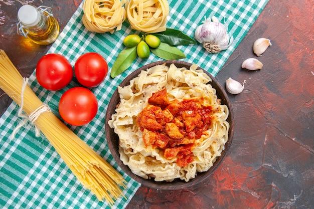 Vista dall'alto gustoso impasto cotto con pollo e pomodori su un piatto di pasta di superficie scura