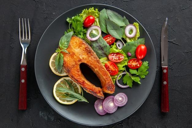 Вид сверху вкусной приготовленной рыбы со свежими овощами и столовыми приборами на темном столе