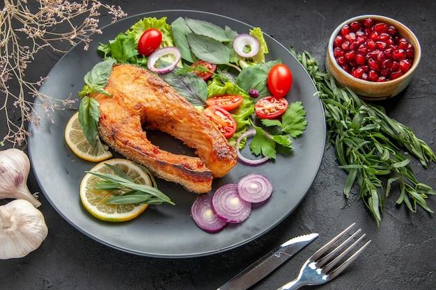 어두운 테이블에 신선한 야채와 조미료를 곁들인 맛있는 요리 생선