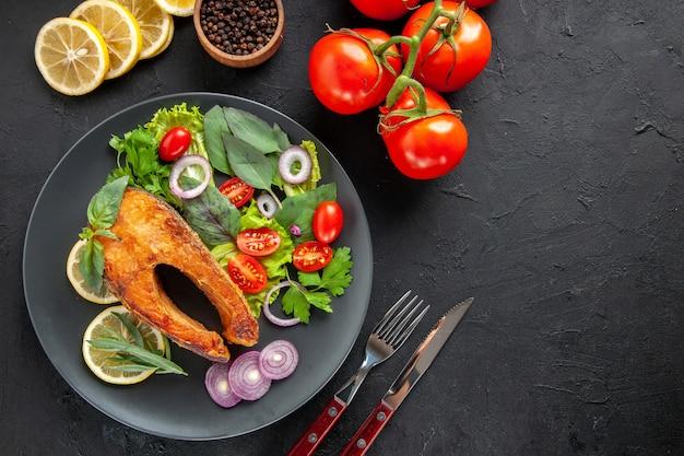 Vista dall'alto gustoso pesce cotto con verdure fresche e posate su un tavolo scuro