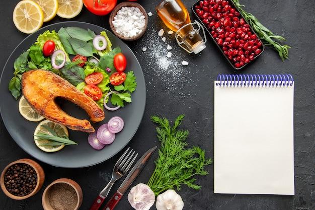 Vista dall'alto gustoso pesce cotto con verdure fresche su un tavolo scuro