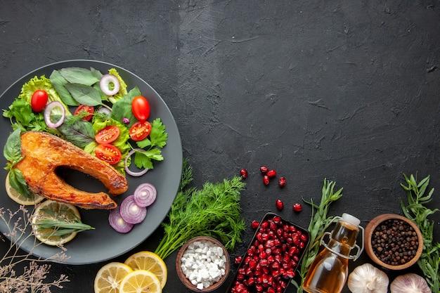 Vista dall'alto gustoso pesce cotto con verdure fresche sul tavolo scuro