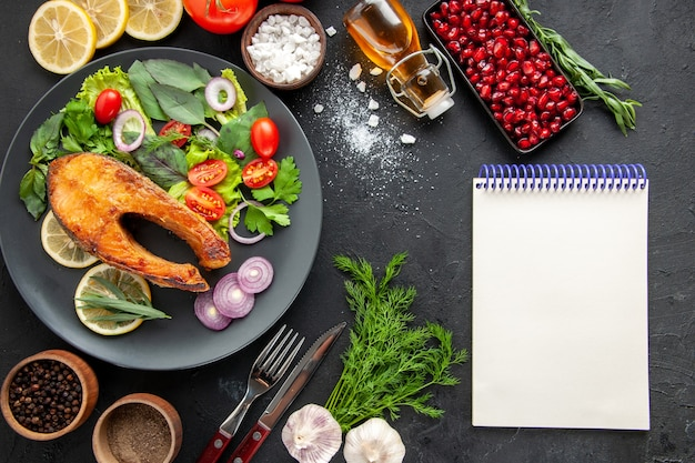 暗いテーブルの上に新鮮な野菜とおいしい調理された魚の上面図