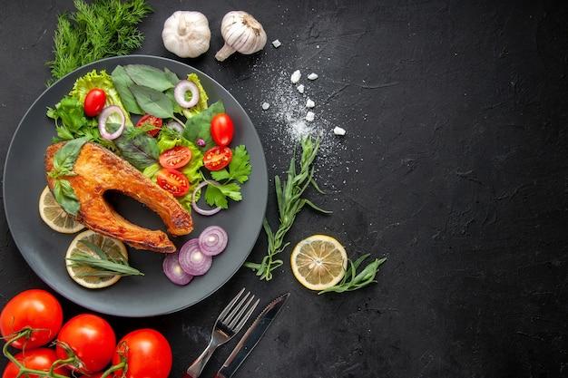Вид сверху вкусной приготовленной рыбы со свежими овощами на темном столе