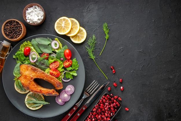 어두운 탁자에 신선한 야채를 곁들인 맛있는 요리 생선