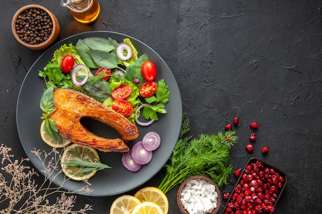 Vista dall'alto gustoso pesce cotto con verdure fresche e condimenti sul tavolo scuro