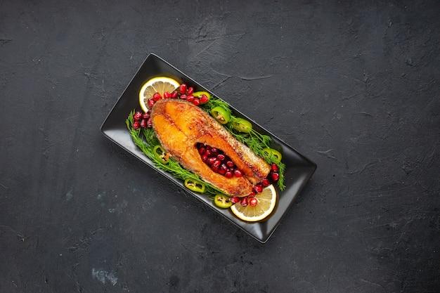 어두운 탁자에 있는 팬 안에 채소와 석류를 넣은 맛있는 요리된 생선