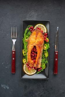 Vista dall'alto gustoso pesce cotto con verdure e fette di limone all'interno della padella sul tavolo scuro