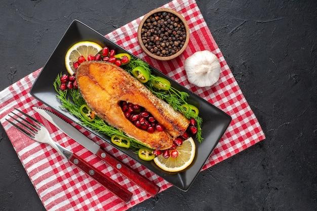 暗いテーブルの上のレモンと緑のおいしい調理された魚の上面図