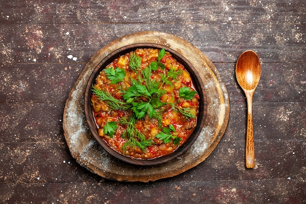 Вид сверху вкусной приготовленной еды, состоящей из нарезанных овощей и зелени на коричневой деревенской столовой еде, соусе, супе