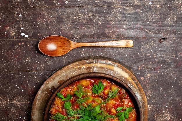 上面図おいしい調理済みの食事は、茶色の素朴な机の上のスライスした野菜と緑で構成されています食事ソーススープ食品野菜のカロリー
