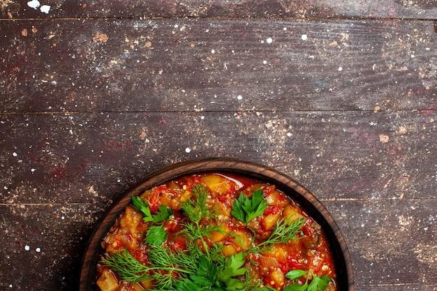 Vista dall'alto gustoso pasto cucinato composto da verdure a fette e verdure sul marrone rustico scrivania pasto salsa zuppa di verdure caloriche alimentari