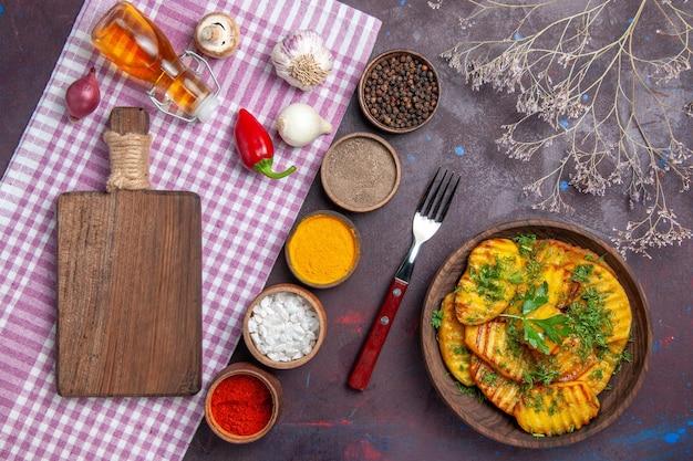 トップビューおいしい調理済みポテトダークデスクディナークッキングミールポテトディッシュにグリーンと調味料を使ったおいしい料理
