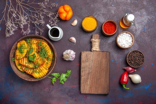 Vista dall'alto gustose patate cotte pasto delizioso con verdure su superficie viola scuro piatto per cena piatto di patate