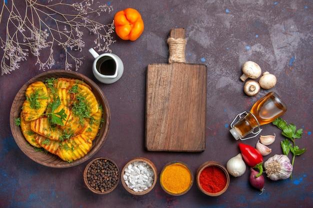 Vista dall'alto gustose patate cotte pasto delizioso con verdure e condimenti sulla superficie scura piatto di patate per la cena