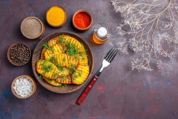 Вид сверху вкусный приготовленный картофель с зеленью и разными приправами на темной поверхности блюдо для ужина, приготовление чипсов из картофеля