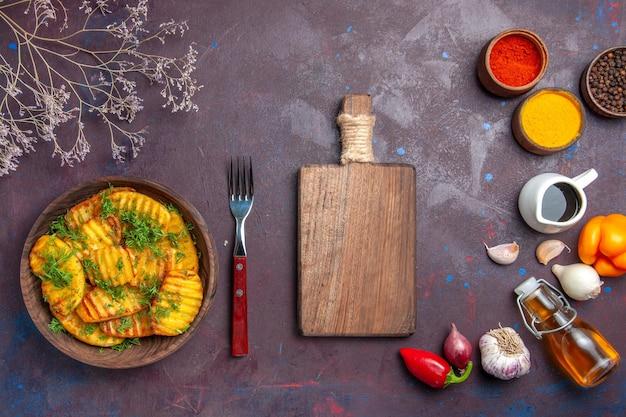 Vista dall'alto gustose patate cotte con verdure su un piatto da pranzo scuro da scrivania con patatine fritte