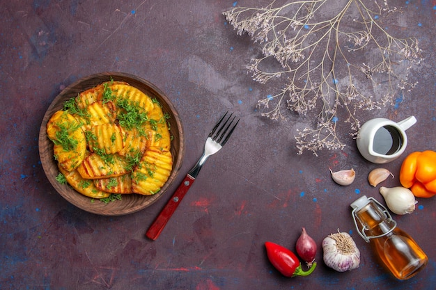Vista dall'alto gustose patate cotte con verdure sulla superficie scura, piatto per cena, patatine fritte, cottura