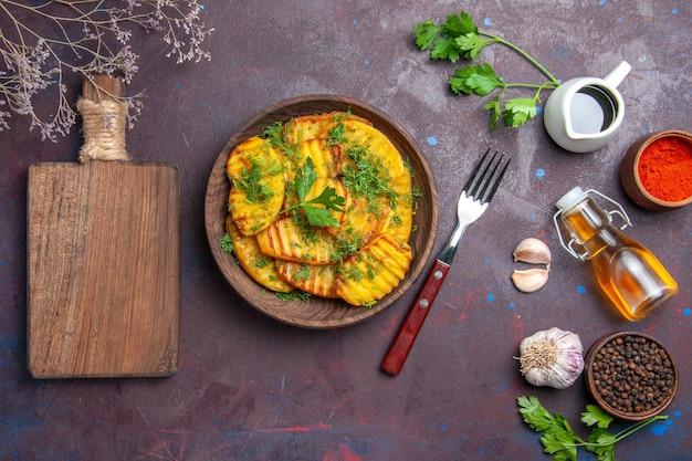 Vista dall'alto gustose patate cotte con verdure sulla superficie scura piatto per la cena con patate fritte