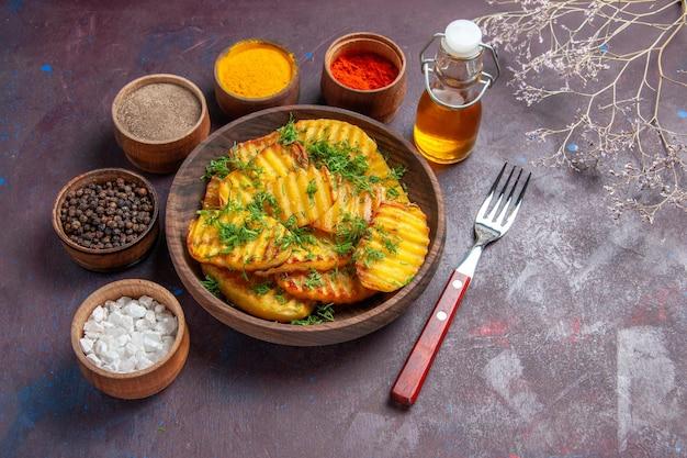 Vista dall'alto gustose patate cotte con verdure e condimenti diversi su superficie scura, piatto per cena, patatine fritte, cottura