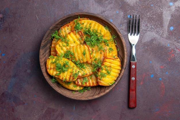 Vista dall'alto gustose patate cotte con verdure all'interno di un piatto marrone sulla superficie scura che cucina patatine fritte cibo cena