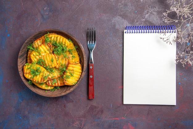 Вид сверху вкусный приготовленный картофель с зеленью внутри коричневой тарелки на темном столе, приготовление чипсов, обед, еда, картофель