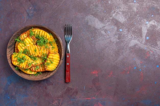 Вид сверху вкусный приготовленный картофель с зеленью внутри коричневой тарелки на темной поверхности, приготовление чипсов, ужин, еда, картофель