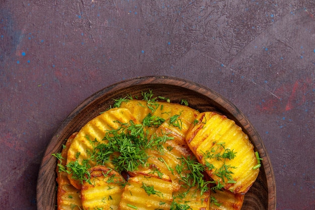 Vista dall'alto gustose patate cotte con verdure all'interno del piatto su una scrivania scura che cucina patatine fritte cibo cena