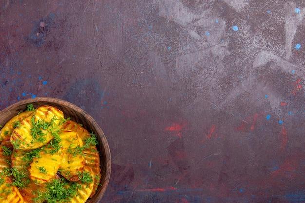 Vista dall'alto gustose patate cotte con verdure all'interno del piatto su una scrivania scura che cucina cibo per cena con patatine fritte
