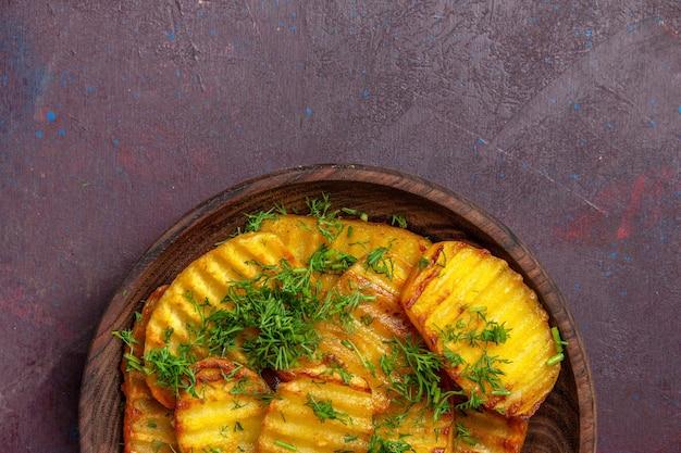 トップビューダークデスククッキングシプディナーフードポテトのプレートの内側に緑のおいしい調理済みポテト
