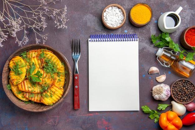 Вид сверху вкусный приготовленный картофель с зеленью на темном столе, картофельное обеденное блюдо, чипсы для приготовления еды