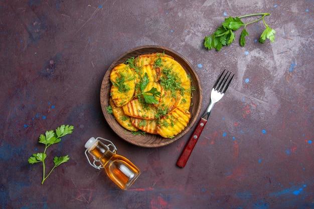 Вид сверху вкусный приготовленный картофель с зеленью на темном столе.