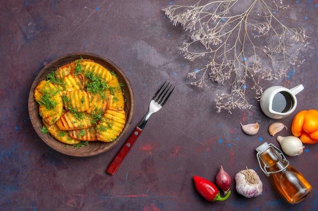 Вид сверху вкусный приготовленный картофель с зеленью на темной поверхности блюдо для ужина, чипсы для приготовления картофеля
