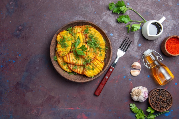 Вид сверху вкусный приготовленный картофель с зеленью на темной поверхности блюдо из картофеля для ужина, чипсы для приготовления еды