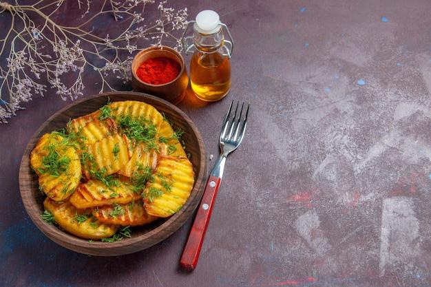 Вид сверху на вкусный приготовленный картофель с зеленью на темной поверхности.