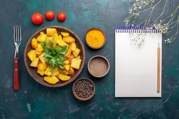 Vista dall'alto gustose patate cotte con condimenti su sfondo blu scuro