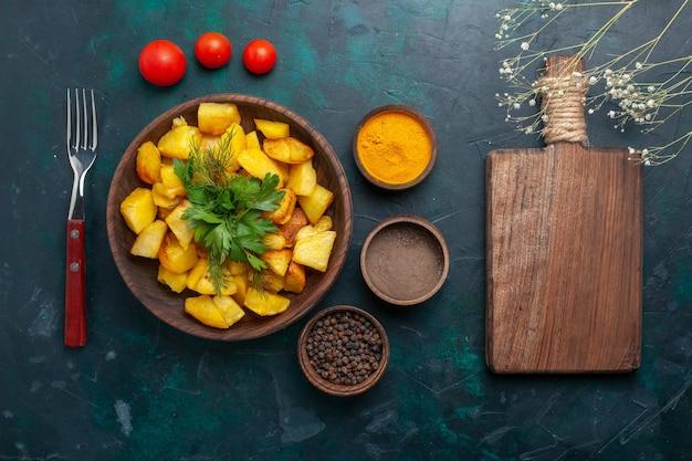 진한 파란색 책상에 조미료와 함께 맛있는 요리 감자를 봅니다.