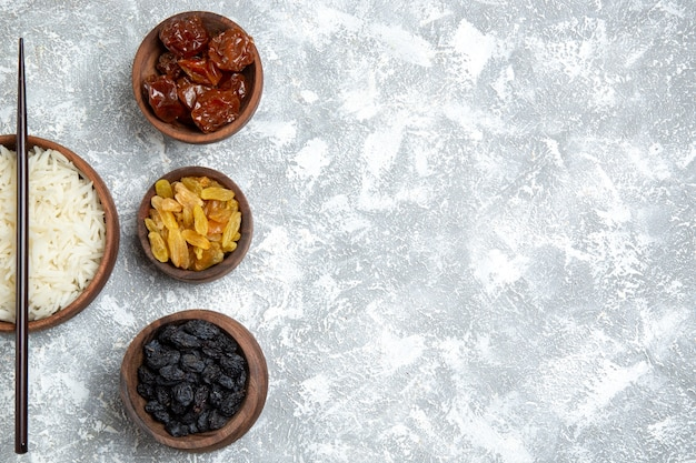 Vista dall'alto gustoso riso cotto all'interno del piatto marrone con uvetta su bianco chiaro