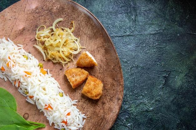 Vista dall'alto gustoso riso cotto con foglie verdi fagioli e carne all'interno del piatto sulla scrivania scura