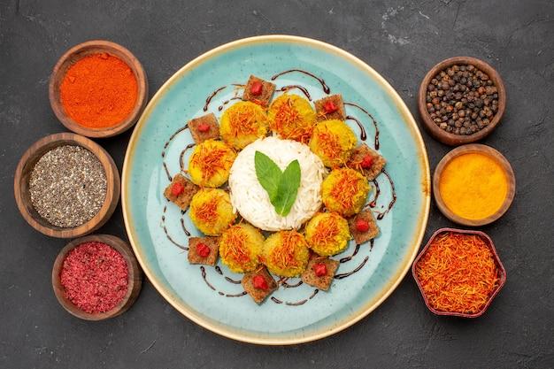 Vista dall'alto di gustoso riso cotto con polpette e condimenti diversi sul tavolo nero